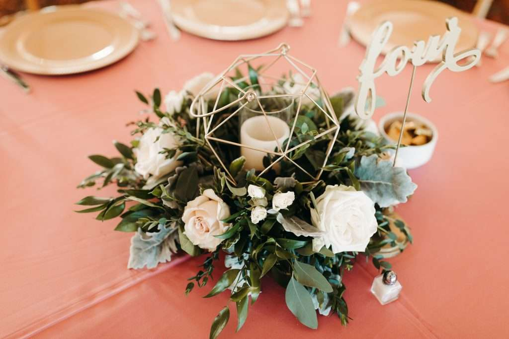 Centerpiece with geometric candle at Riverhouse wedding